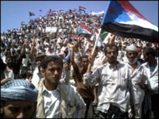متظاهرون يرفعون العلم اليمني