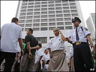 Funcionários de hotel e segurança esperam terremoto passar antes de volta ao prédio onde trabalham