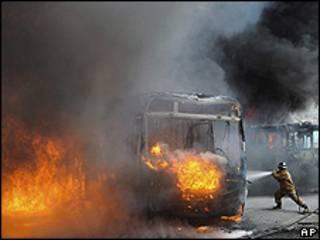 Bombeiro tenta apagar incêndio em ônibus queimado na Zona Norte do Rio