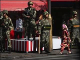 صبية من الويجور تمر امام جنود صينيين