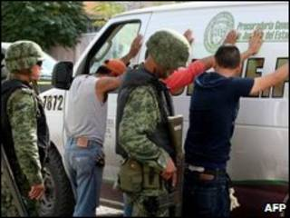 Soldados mexicanos revistam suspeitos perto de uma cena de assassinato em Ciudad Juarez