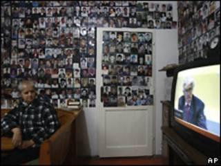 Una mujer bosnia de Srebrenica mira en TV el juicio de Karadzic. De fondo una pared cubierta con víctimas de la masacre de Srebrenica