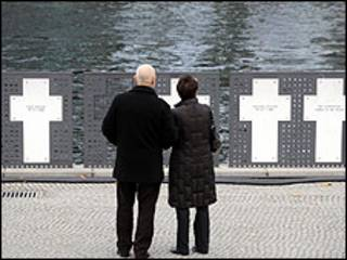 a couple reads the names of east germans who died trying to cross the berlin wall