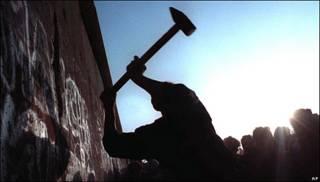 Gente picando el Muro de Berlín