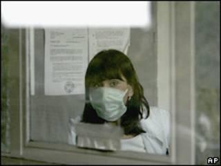 Женщина в маске за стеклом в Сербии