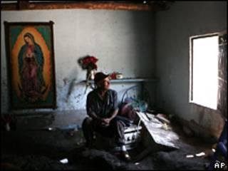 Un hombre mira su casa dañada por las inundaciones en El Salvador