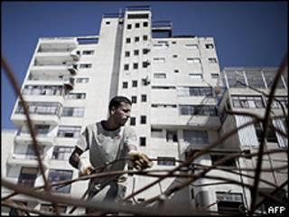 Homem coleta ferragens em frente ao hospital Al-Quds, na Cidade de Gaza, danificado pela ofensiva israelense