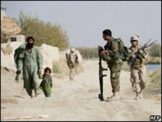 阿富汗哈爾曼德省一對父女走過在巡邏的美國海軍陸戰隊與阿富汗軍隊士兵(24/11/2009)