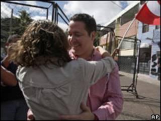 Carlos Reina, assessor de Zelaya, abraça a mulher ao deixar a embaixada do Brasil nesta terça-feira (AP)