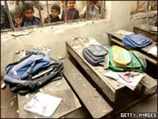 Niños observan el impacto que dejó una bomba en una escuela de Bagdad
