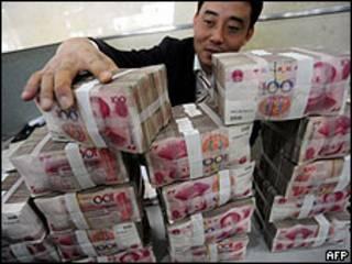 Un hombre, junto a billetes de yuan, la moneda china