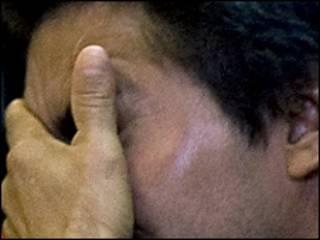 Un hombre cubriéndose el rostro / Foto de archivo