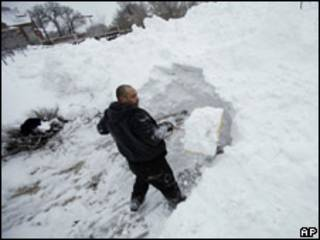 Homem retira neve de calçada na cidade de Des Moines, Iowa, nesta sexta-feira (AP)