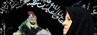 Una mujer iraní delante de una imagen del imán Hussein, nieto del profeta Mahoma