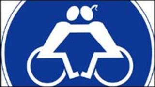 نشان گرافیکی دو معلول زن و مرد که بر روی ویلچر نشسته و همدیگر را در آغوش گرفته اند