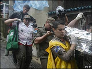 Socorristas en Rio de Janeiro llevan a una víctima de las inundaciones.