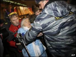 Сотрудник милиции задерживает Людмилу Алексееву