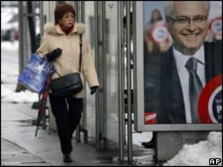 Женщина идет мимо предвыборного плаката