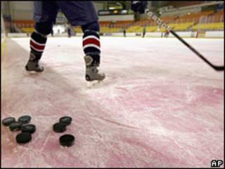 Хоккеист и шайбы на льду (архивное фото)