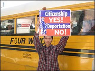Joven inmigrante sostiene un cartel alusivo.
