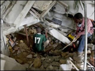 Haitianos trabalham no resgate de vítimas em Porto Príncipe (AFP, 14 de janeiro)