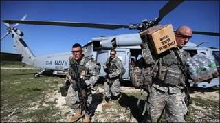 Soldados americanos desembarcam alimentos para ajuda humanitária no Haiti