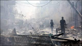 Pessoas caminham entre escombros em Porto Príncipe