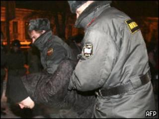 Два милиционера ведут участника митинга в Москве 19 января 2010 года