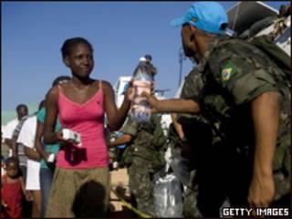 Foto divulgada pela Minustah mostra militar brasileiro entregando água para haitiana (Getty Images, 22 de janeiro)