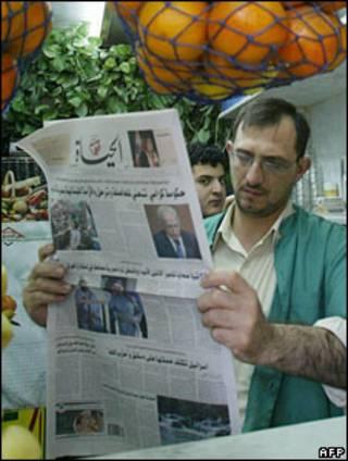 یک آبمیوه فروش در دمشق در حال خوانده روزنامه