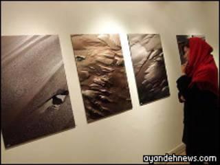 تصویر هدیه تهرانی در حال نگاه کردن به تابلو های نمایشگاهش