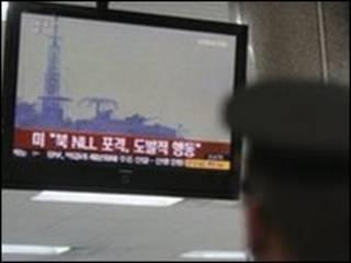 Người dân theo dõi tivi về vụ bắn đạn pháo