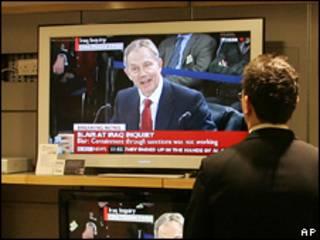 Hombre viendo el testimonio de Tony Blair en TV.