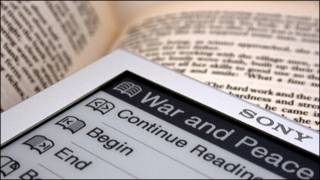 Dos libros, el de papel y el electrónico convivendo en la biblioteca