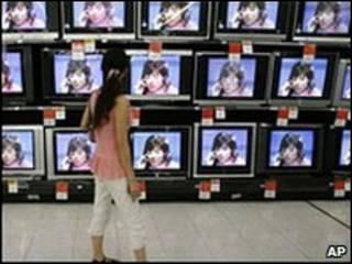 Mujer frente a televisores en China