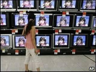 Một phụ nữ đi ngang qua cửa hàng bán TV ở Vũ Hán