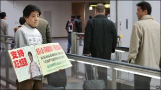 Feng Zhenghu mostra cartazes a passageiros em Tóquio