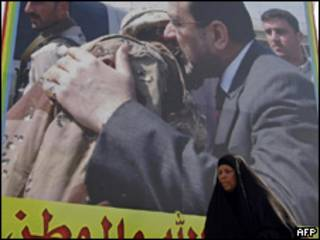 Una mujer pasa frente a un cartel de campaña del primer ministro Nouri al-Maliki