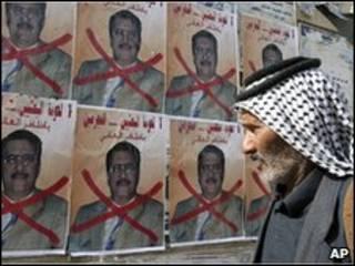مردم عراقی به پوستر یک نامزد ممنوع شده نگاه می کند