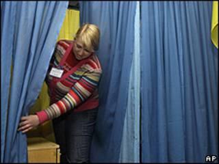 Funcionaria electoral prepara sitio de votación en Ucrania.