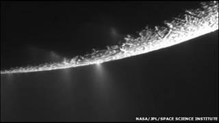 Partículas de gelo e vapor de água espirram por entre rachaduras na superfície da lua de Saturno