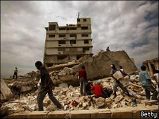 Haitianos sobre escombros de edifício desabado em Porto Príncipe