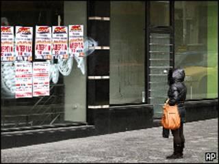 Mulher olha posteres da greve em fachada de loja fechada em Atenas