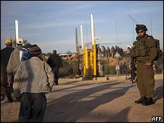 Soldado israelense observa trabalhadores palestinos em ponto de checagem na Cisjordânia