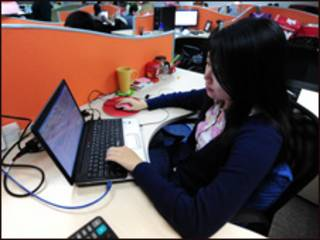 شابة تجلس الى كمبيوتر