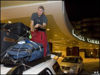 Un hombre coloca sus pertencia sobre un vehículo en un hotel de Hawaii