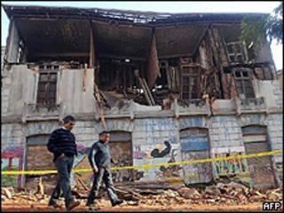 Moradores de Valparaiso, Chile, passam em frente a prédio destruído