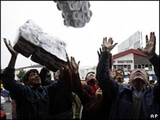 Moradores de Concepcion recebem produtos saqueados de supermercado