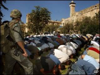 Soldado israelense vigia palestinos muçulmanos rezando (AP/Nasser Shiyoukhi)