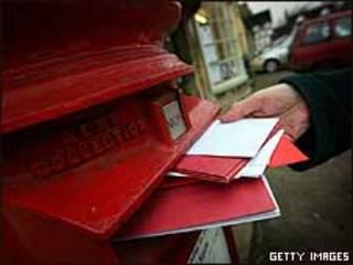 Buzón londinense y cartas que se aprestan a entrar